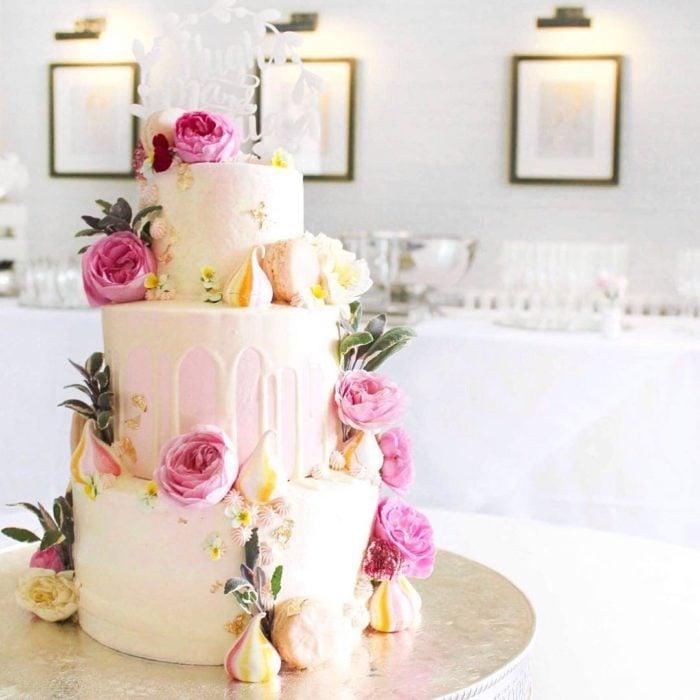 pastel de tres pisos blanco y flores rosas
