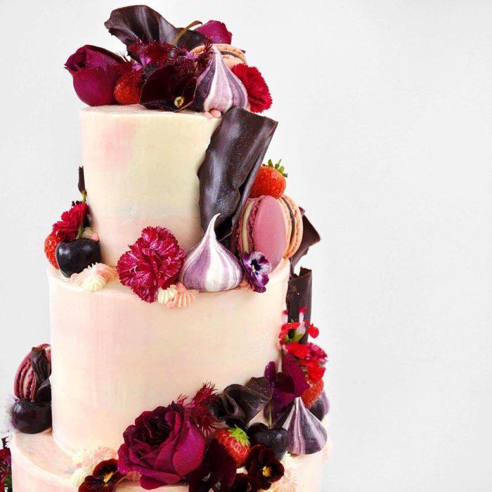 pastel rosa con blanco y flores rojas