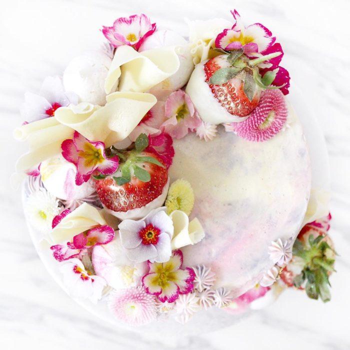 pastel blanco con flores rosas y fresas