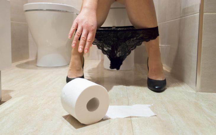 mujer piernas separadas y papel de baño