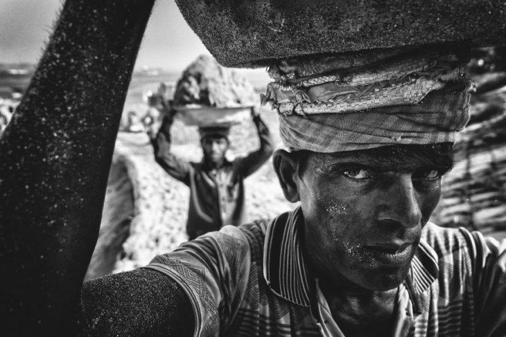 hombre cargando arena en Munshiganj, Bangladesh