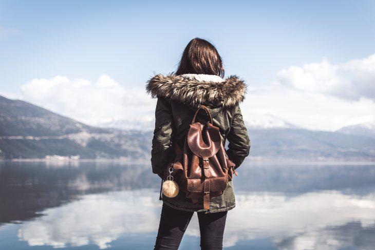 chica con mochila en un lago