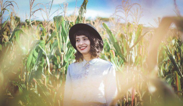chica sonriendo en un campo de maiz