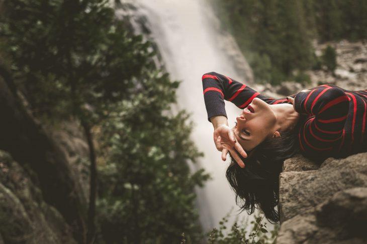 chica recostada en una roca