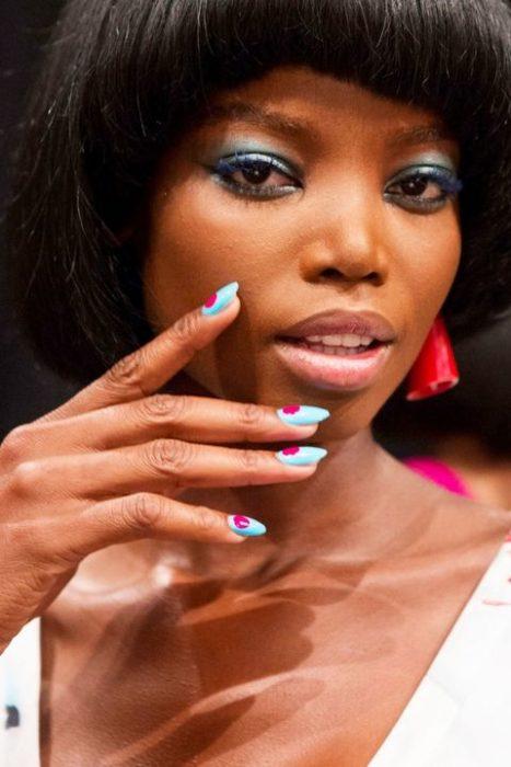uñas azul claro con puntos rosados