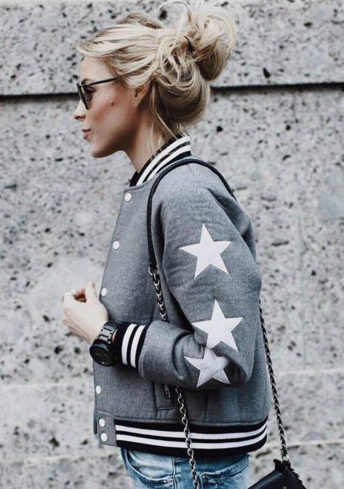 Chica usando una bomber jacket gris con estrellas