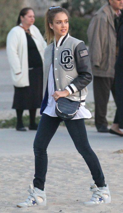 Chica usando una bomber jacket estilo universitaria