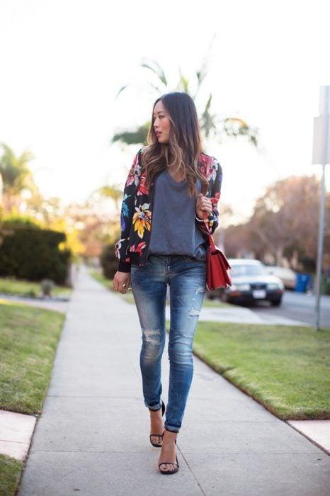 Chica usando una bomber jacket negro con estampados florales