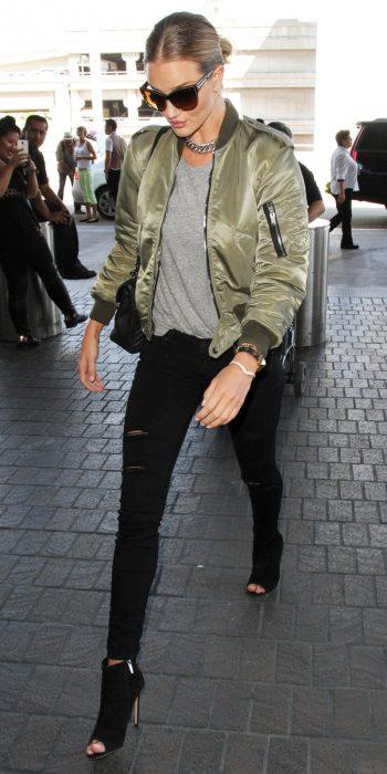 Rosie Huntington usando una bomber jacket verde mientras camina en el aeropuerto