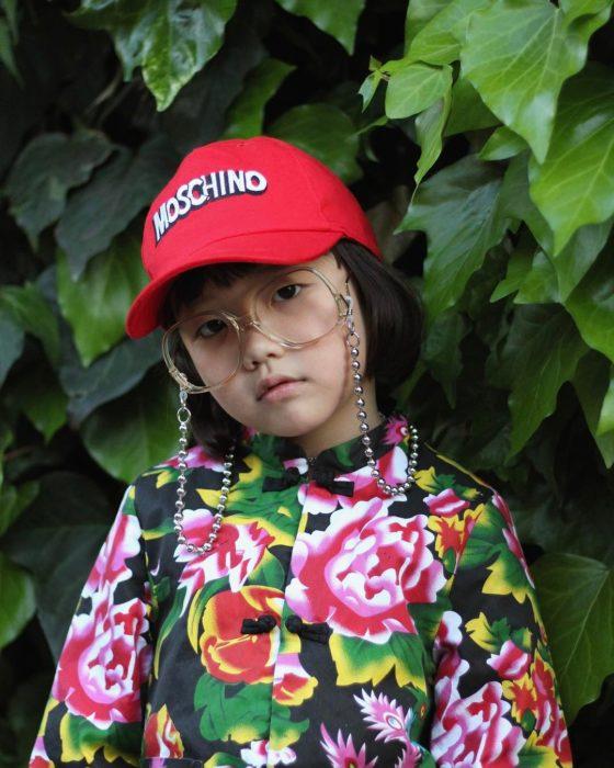 Niña de 6 años vistiendo gorra, gafas y blusa con flores
