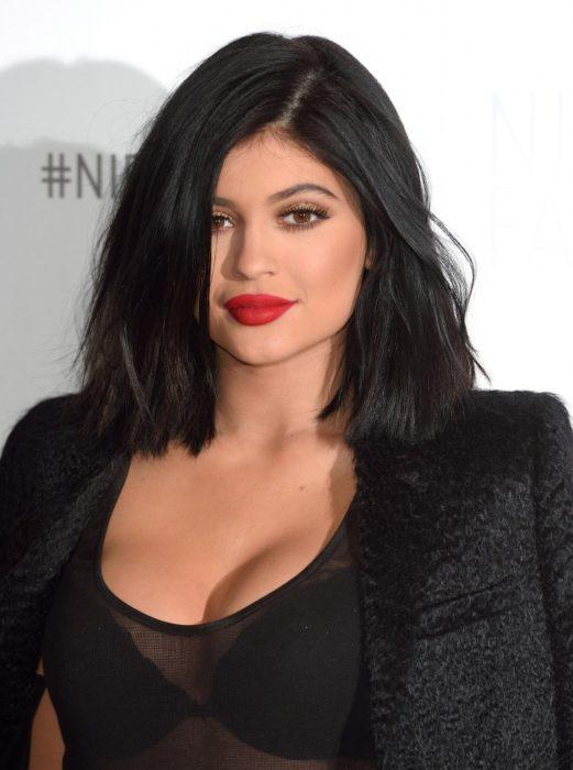 Kylie jenner en 2015 usando un outfit negro con blazer y labios rojos