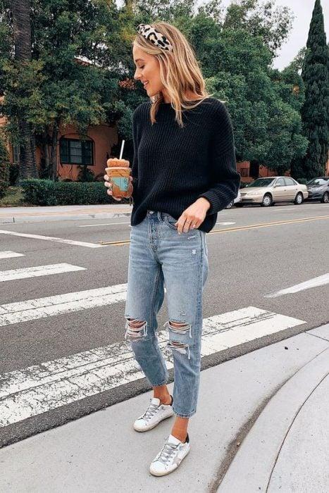 chica rubia con café en mano, suéter negro y jeans rasgados