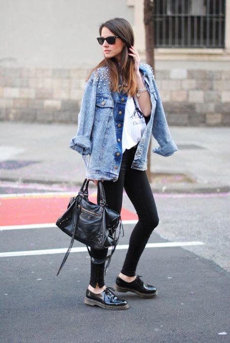 Chica usando leggings chamarra de mezclilla y blusa blanca