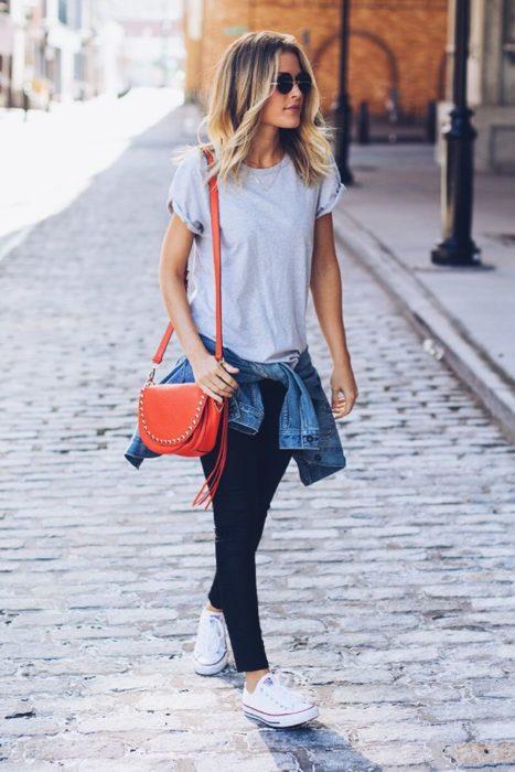 Chica usando unos leggings chamarra de mezclilla atada a la cintura y blusa color gris