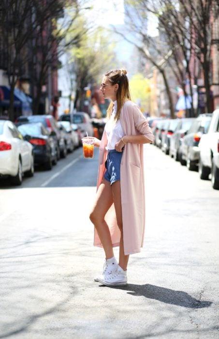 Chica usando tenis blancos shorts y suéter color rosa palo