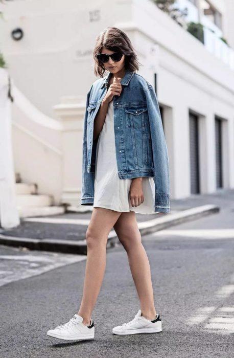 Chica usando un vestido de color blanco con una chaqueta de mezclilla