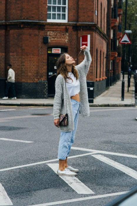 Chica usando unos mom jeans tenis y suéter gris