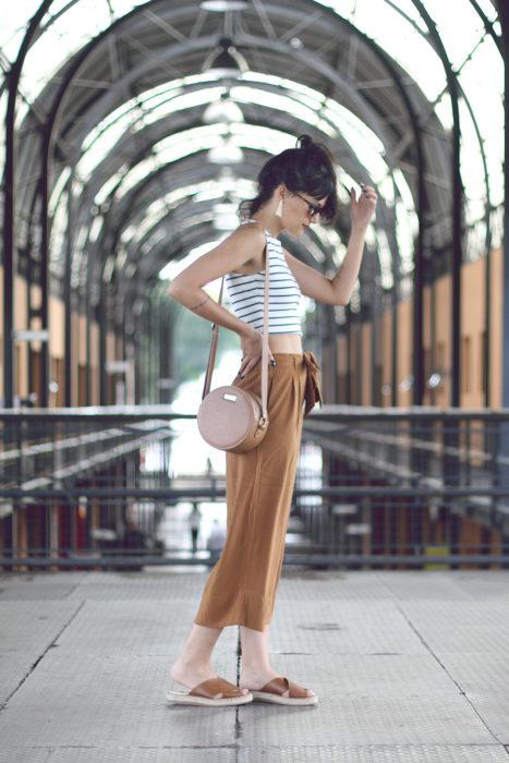 Chica usando un crop top a rayas, pantalón caqui holgado y sandalias