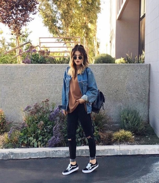 Chica usando jeans rasgados tenis blusa holgada y chamarra de mezclilla