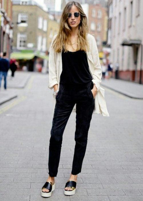 Chica usando un outfit de color negro con un blazer e tonos claros