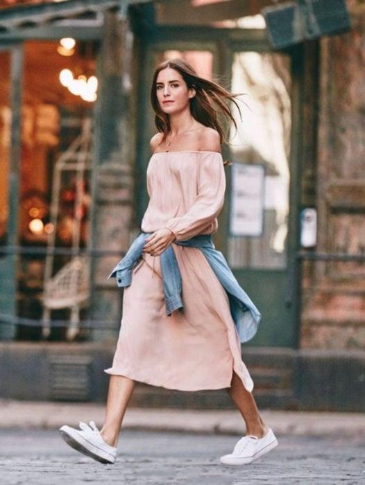Chica usando un maxi vestido de color rosa palo y chaqueta de mezclilla atada a la cintura