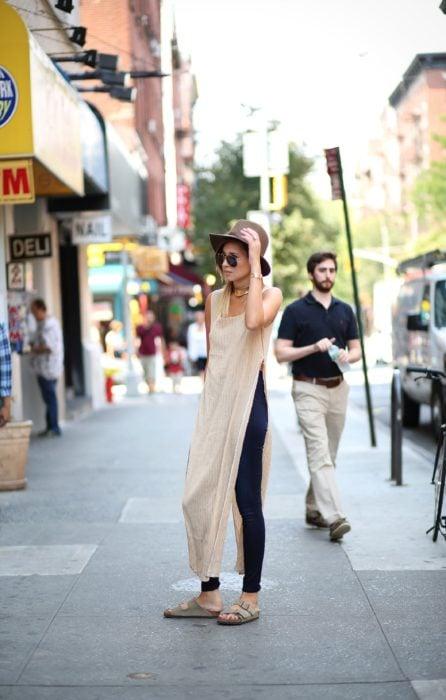 Chica usando una maxiblusa sombrero jeans y sandalias
