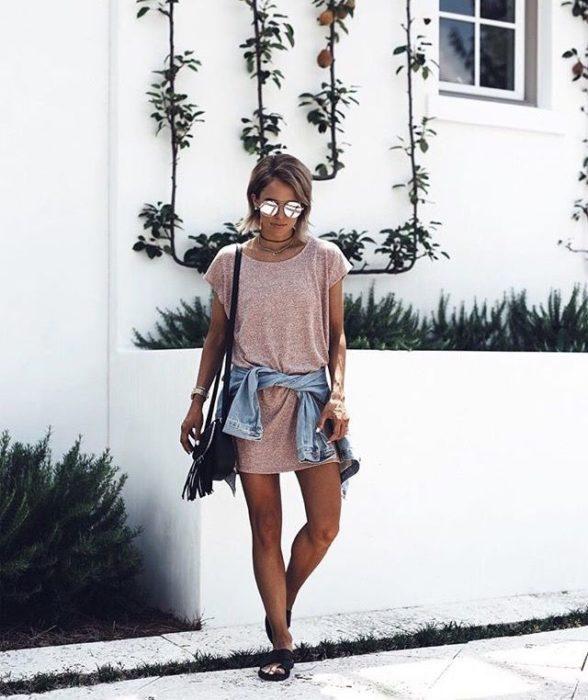Chica usando una chamarra de mezclilla atada a la cintura y un blusón con tenis