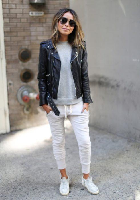 Chica usando jogger pants blancos, chamarra de piel negra y sudadera