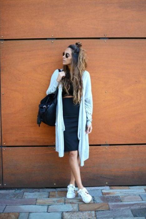 Chica usando una falda de lápiz negra y un crop top y suéter de color azul