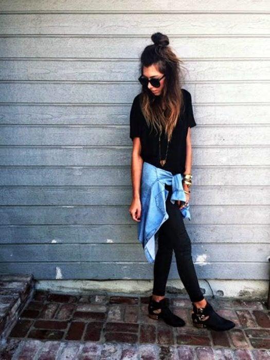 Chica usando una blusa de mezclilla con jeans negros