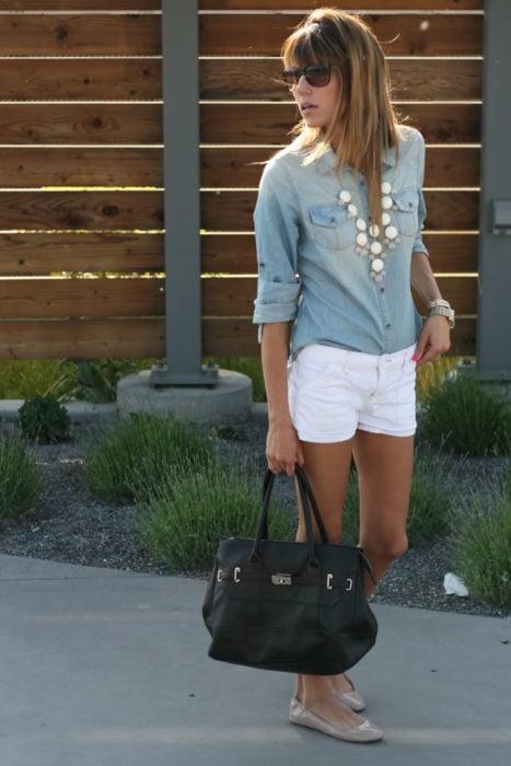 Chica usando una blusa de mezclilla con shorts blancos