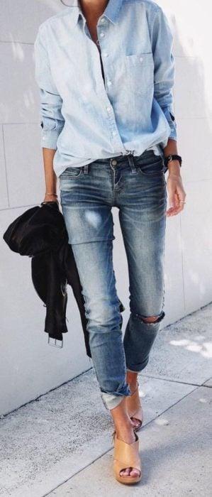 Chica usando una blusa de mezclilla con jeans rasgados