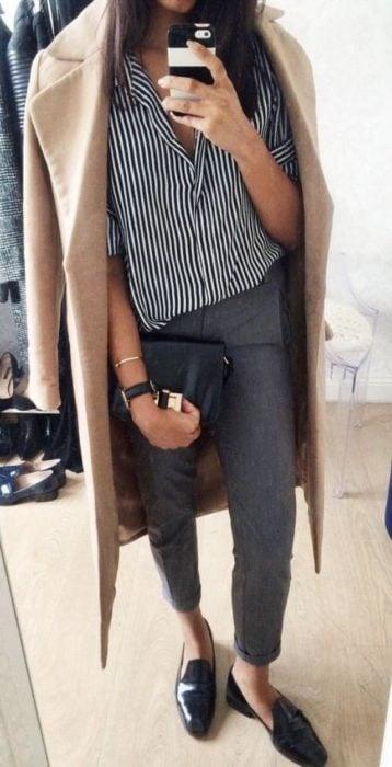Chica usando mocasines con jeans grices, blusa rayada y gabardina beige