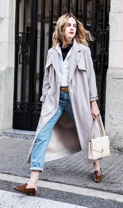 Chica usando mocasines con gabardina jeans y blusa de vestir blanca