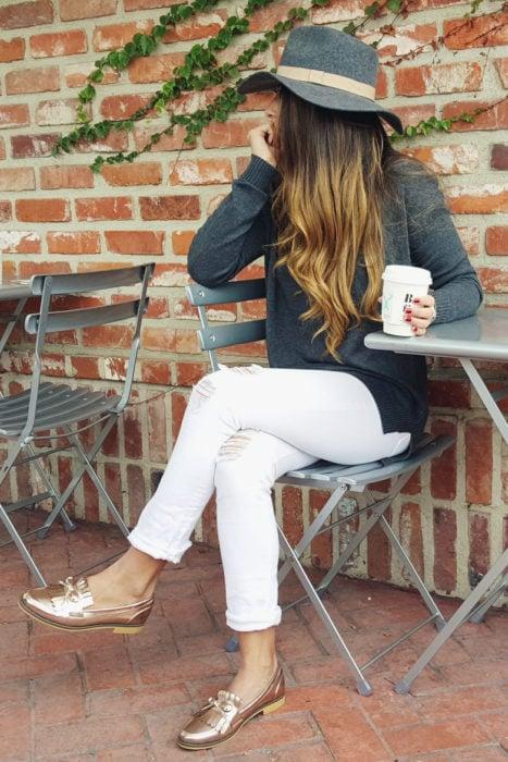 Chica usando mocasines con pantalón blanco y cardigan gris