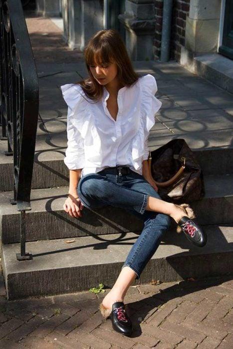 Chica usando mocasines con jeans y blusa blanca