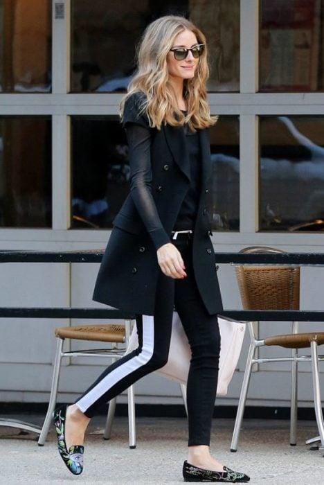 Chica usando mocasines negros con leggins rayados