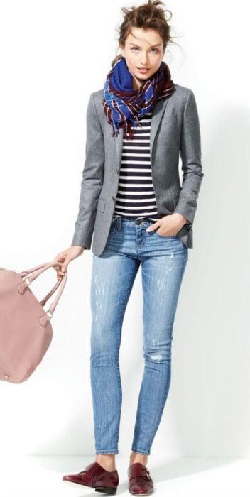 Chica usando mocasines con blazer gris blusa de rayas y jeans