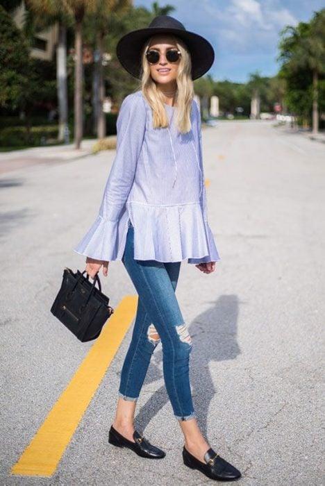 Chica usando mocasines con jeans rasgados y bluson azul marino