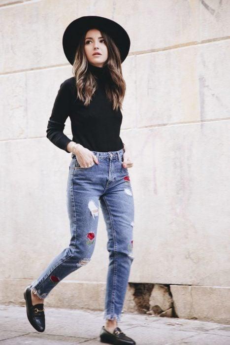 Chica usando mocasines con jeans rasgados y blusa negra