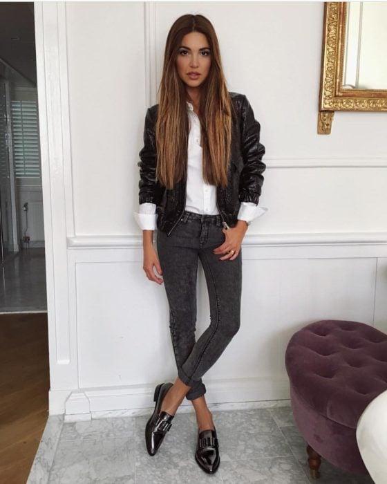 Chica usando mocasines con jeans y chamarra de piel