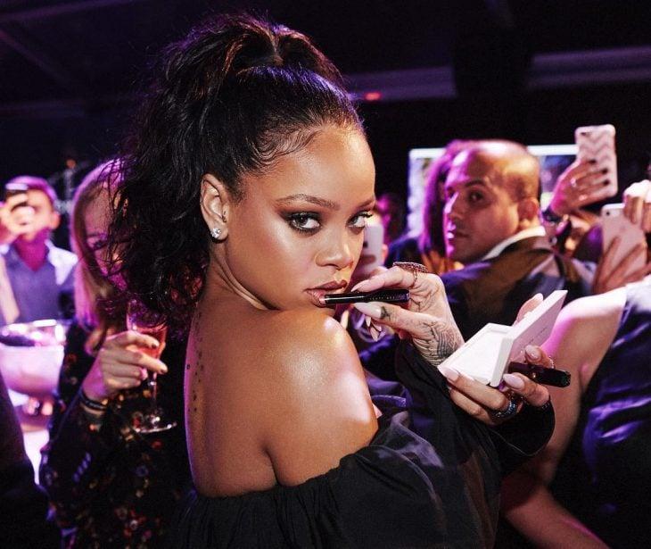 Rihanna posando con un labial de su línea de maquillaje