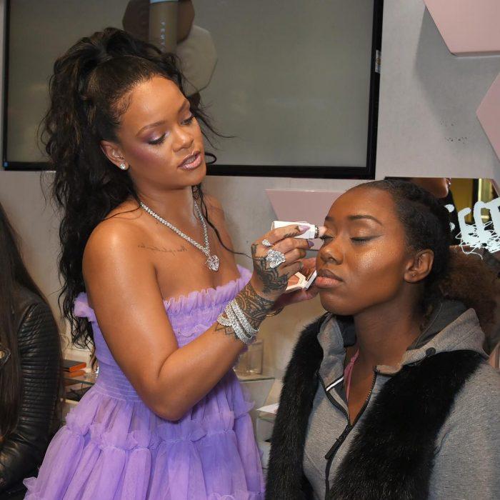 Rihanna aplicando su nuevo maquillaje a una fan
