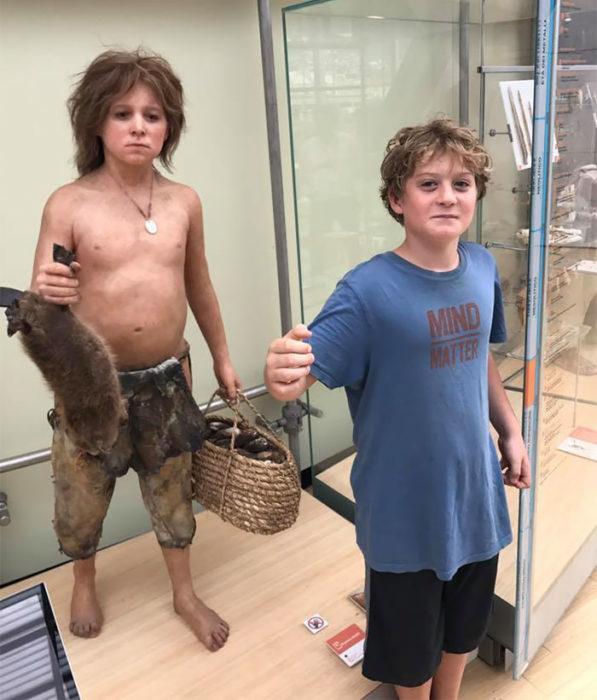 chico imitando a figura en el museo