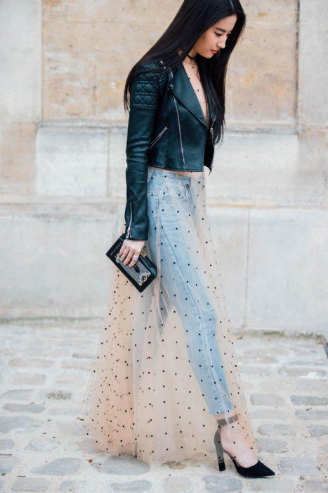 Chica usando un vestido sobre pantalones de mezclilla y una chaqueta de cuero