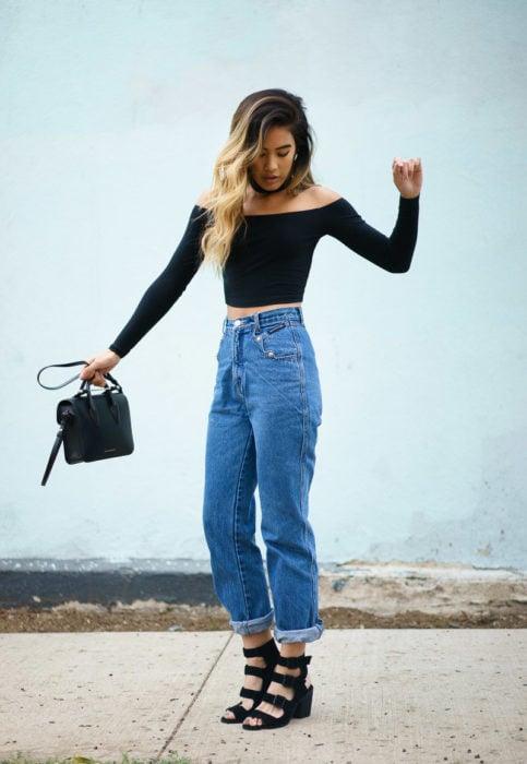 Chica usando unos pantalones de corte alto y blusa negra con choker