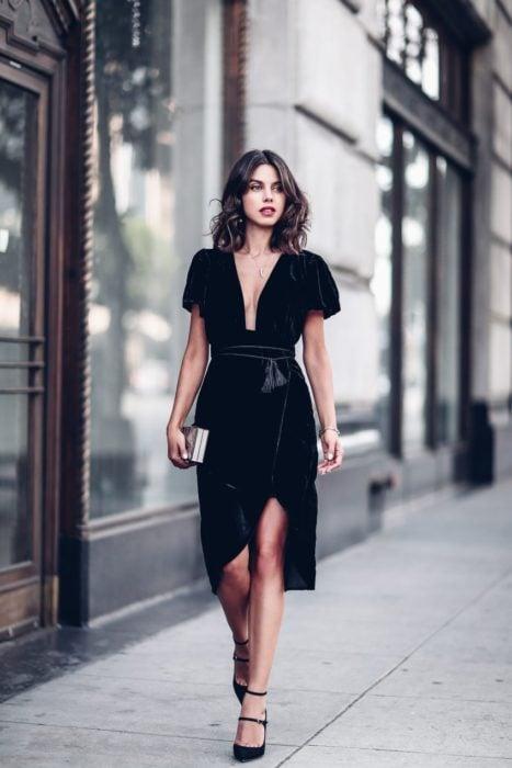 Chica caminando por las calles mientras usa un vestido negro