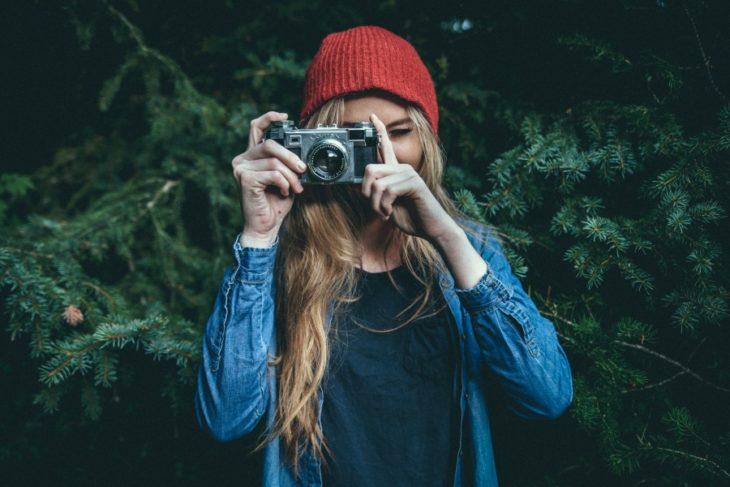 chica tomando fotos en el campo