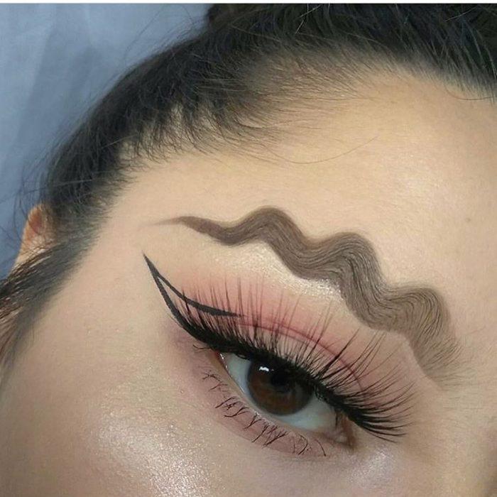 Chica con sus cejas maquilladas en formas de ondas