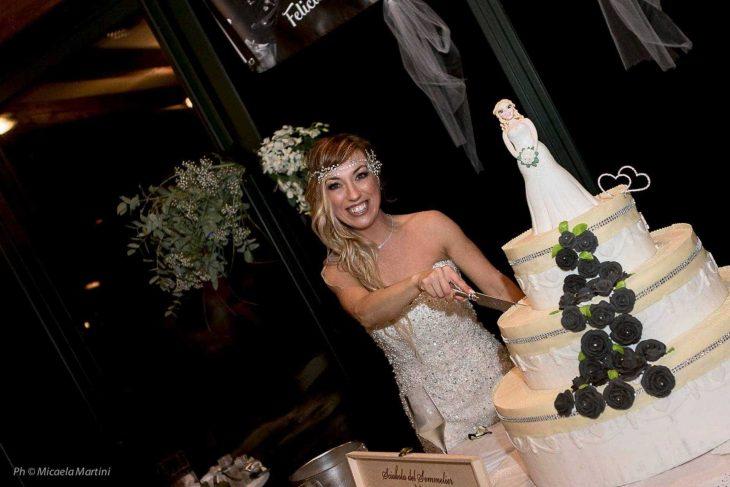 mujer con vestido de novia cortando pastel